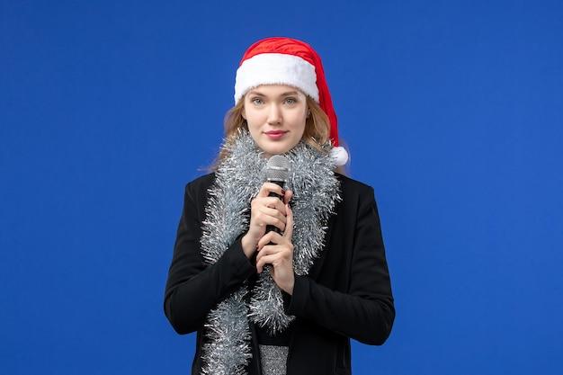 青い壁に新年のカラオケパーティーで若い女性の正面図