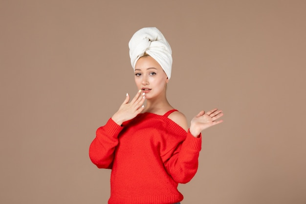 그녀의 머리 갈색 벽에 수건으로 빨간 셔츠에 젊은 여자의 전면 보기