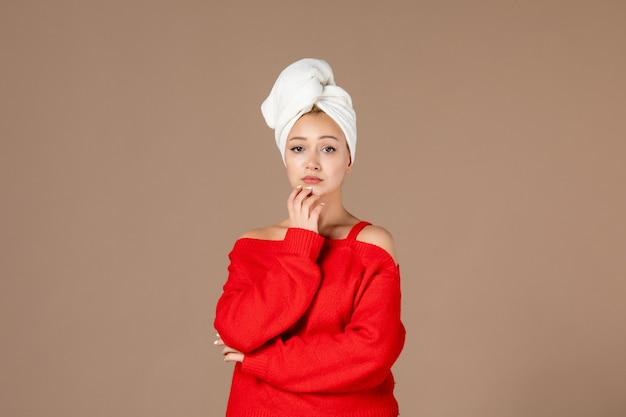 彼女の頭の茶色の壁にタオルと赤いシャツを着た若い女性の正面図