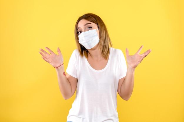 밝은 노란색 벽에 멸균 마스크에 젊은 여자의 전면보기