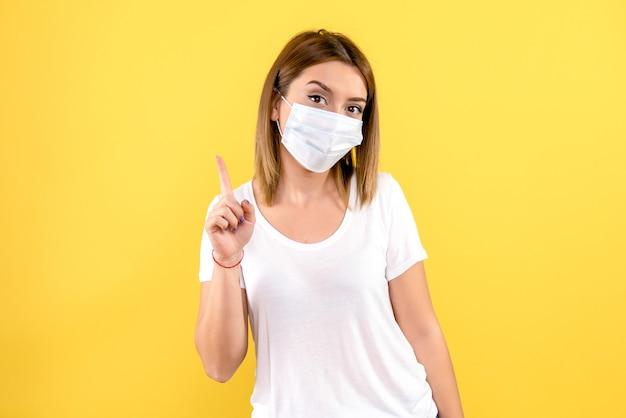 Вид спереди молодой женщины в стерильной маске на желтой стене