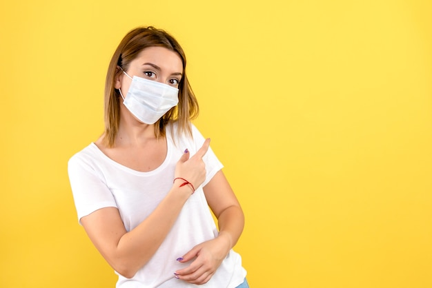 黄色の壁に滅菌マスクで若い女性の正面図
