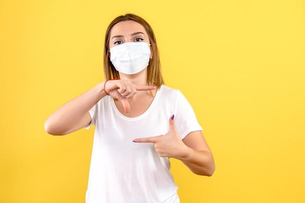 노란색 벽에 살 균 마스크에 젊은 여자의 전면보기