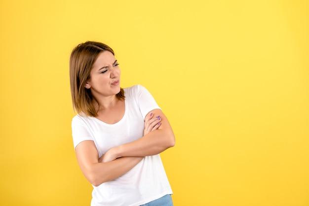 ちょうど黄色の壁にポーズをとって若い女性の正面