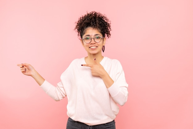 ピンクの壁に微笑んでいる若い女性の正面図