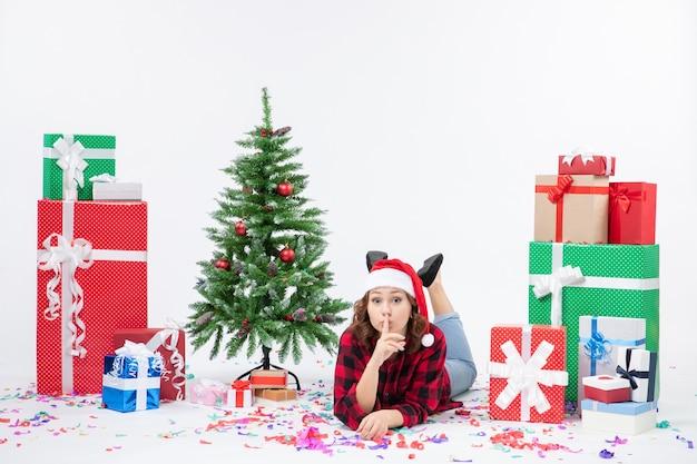 Вид спереди молодой женщины, лежащей вокруг рождественских подарков и маленькой праздничной елки на белой стене