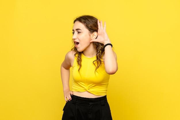 노란색 벽에 밀접 하 게 듣고 젊은 여자의 전면보기