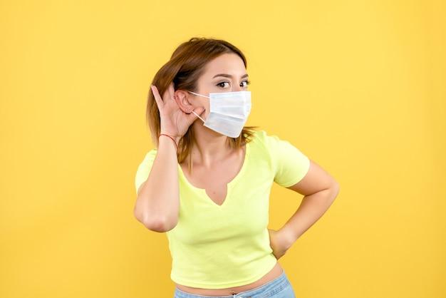 黄色の壁にマスクで聞いている若い女性の正面図