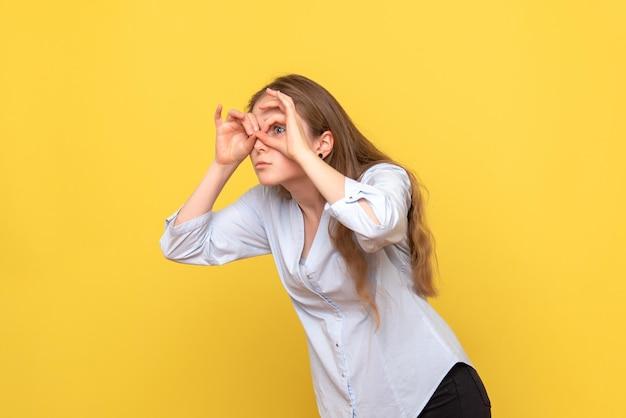 指を通して見ている若い女性の正面図