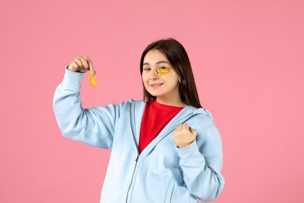 ピンクの壁にフェイスマスクを作る若い女性の正面図