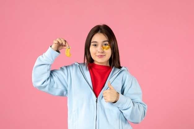 분홍색 벽에 얼굴 마스크를 만드는 젊은 여성의 전면 보기