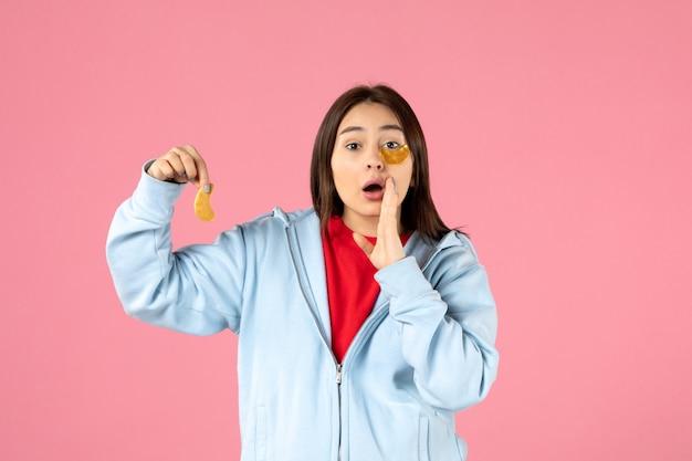 Вид спереди молодой женщины, делающей маску для лица на розовой стене