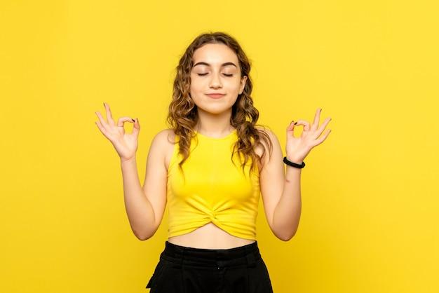 Вид спереди молодой женщины, медитирующей на желтой стене