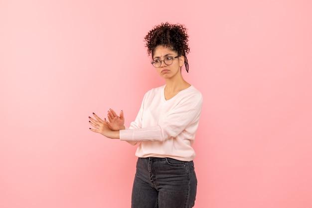 분홍색 벽에 젊은 여자의 전면보기