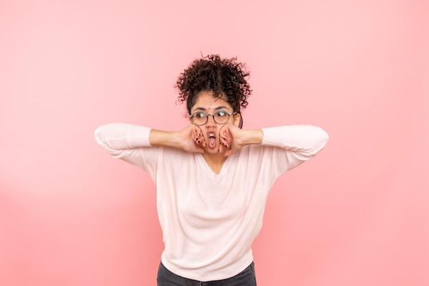 ピンクの壁に若い女性の正面図