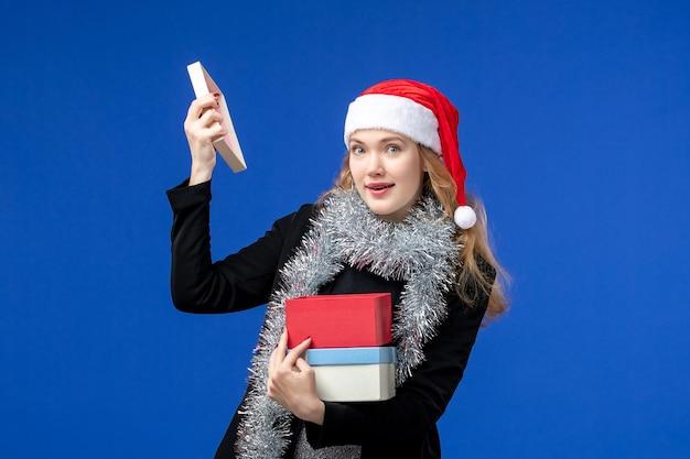 青い壁に新年のプレゼントを開く若い女性の正面図