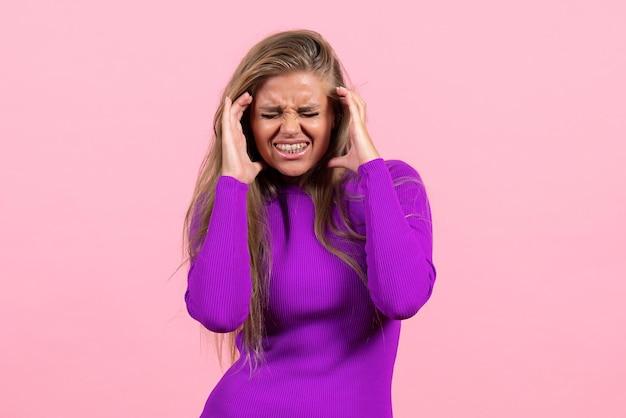 ピンクの壁に美しい紫色のドレスでポーズをとって若い女性の正面図