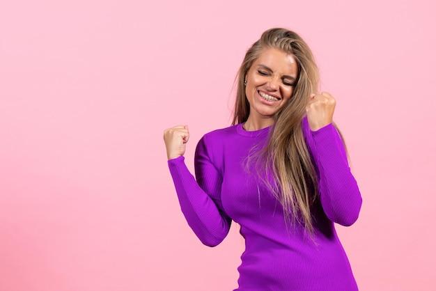 분홍색 벽에 아름다운 보라색 드레스를 입고 기뻐하는 젊은 여성의 전면 모습
