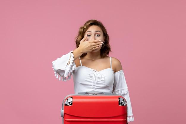 淡いピンクの壁に赤いバッグでポーズをとって若い女性の正面図