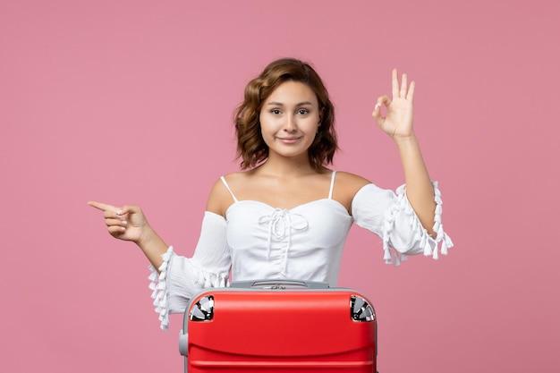 淡いピンクの壁に赤い休暇バッグでポーズをとって若い女性の正面図