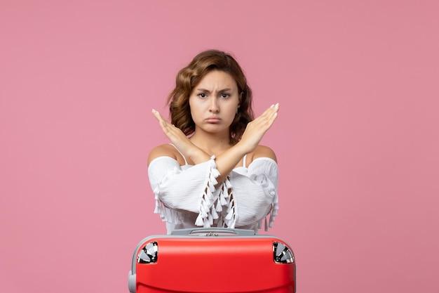 ピンクの壁に赤い休暇のバッグでポーズをとって若い女性の正面図