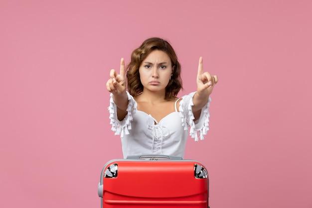밝은 분홍색 벽에 빨간 휴가 가방을 들고 포즈를 취하는 젊은 여성의 전면 보기