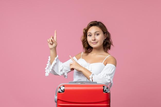 Вид спереди молодой женщины, позирующей с красной туристической сумкой на розовой стене
