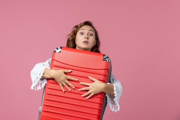 Вид спереди молодой женщины, готовящейся к поездке и держащей красную сумку на розовой стене
