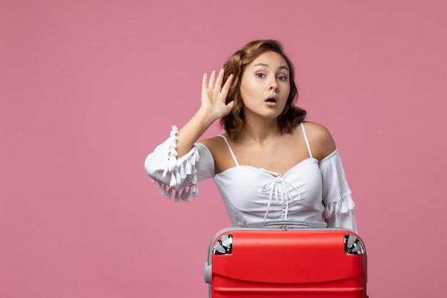 Вид спереди молодой женщины, готовящейся к поездке с красной сумкой на розовой стене