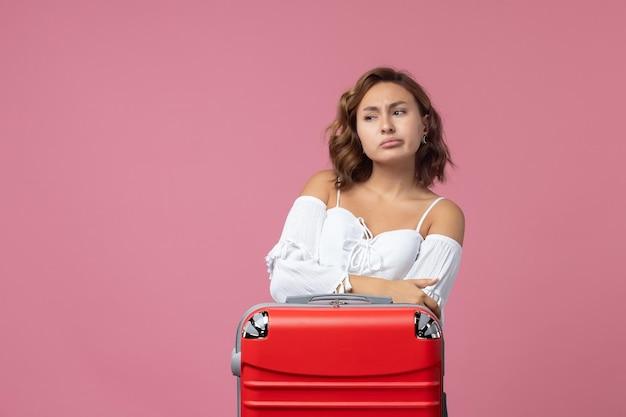 ピンクの壁に赤いバッグと旅行の準備をしている若い女性の正面図