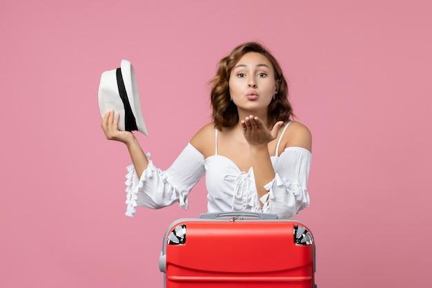 休暇の準備とピンクの壁に帽子をかぶって若い女性の正面図