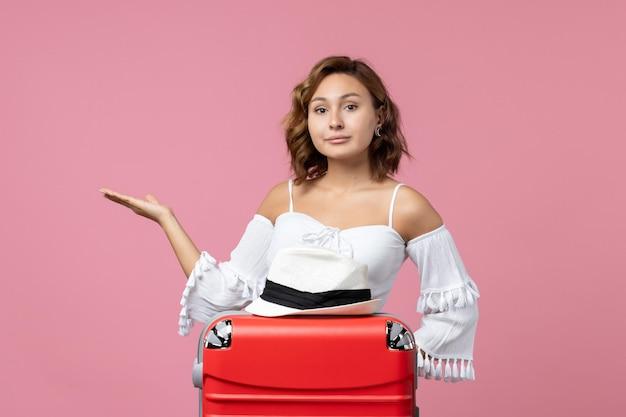 バッグとピンクの壁にポーズをとって休暇の準備をしている若い女性の正面図
