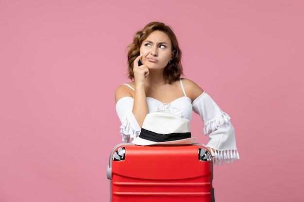Вид спереди молодой женщины, готовящейся к отпуску с красной сумкой, позирующей на розовой стене