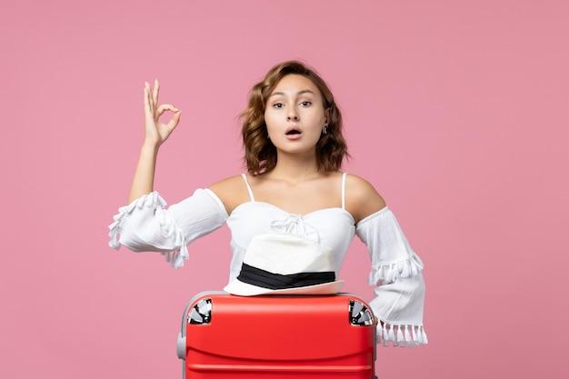 ピンクの壁にポーズをとって赤いバッグと休暇の準備をしている若い女性の正面図