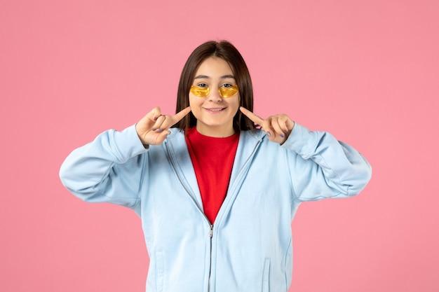 ピンクの壁に彼女の目の下に眼帯を置く若い女性の正面図