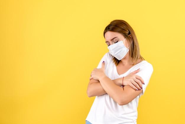 Вид спереди молодой женщины, дрожащей на желтой стене