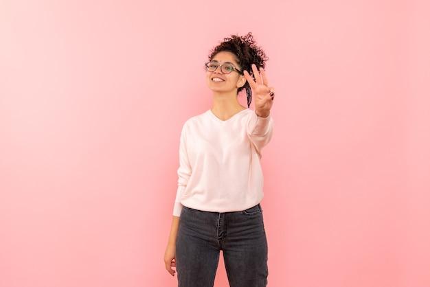 ピンクの壁に数字を示す若い女性の正面図