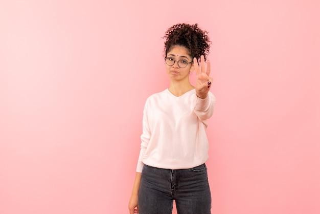분홍색 벽에 번호를 보여주는 젊은 여자의 전면보기