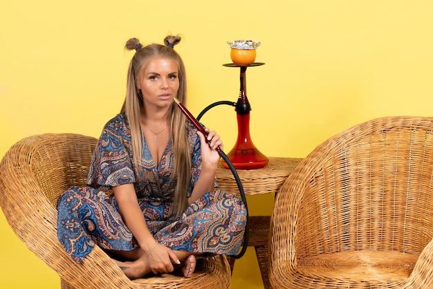 노란색 벽에 앉아서 물담배를 피우는 젊은 여성의 전면 모습