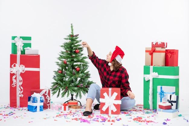 Вид спереди молодой женщины, сидящей вокруг рождественских подарков и маленькой праздничной елки на белой стене