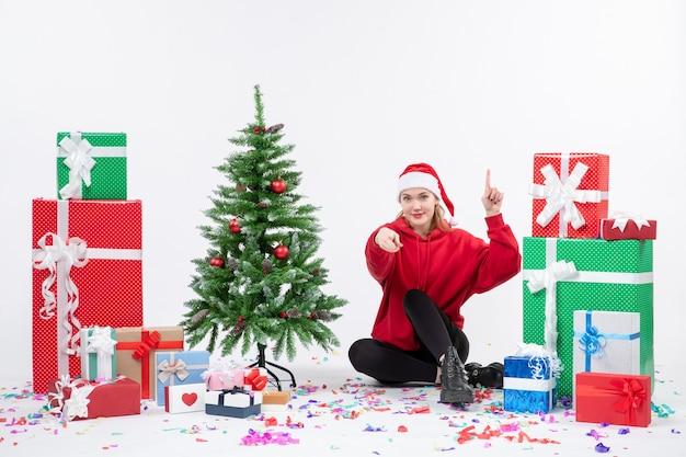 Вид спереди молодой женщины, сидящей вокруг различных праздничных подарков на белой стене