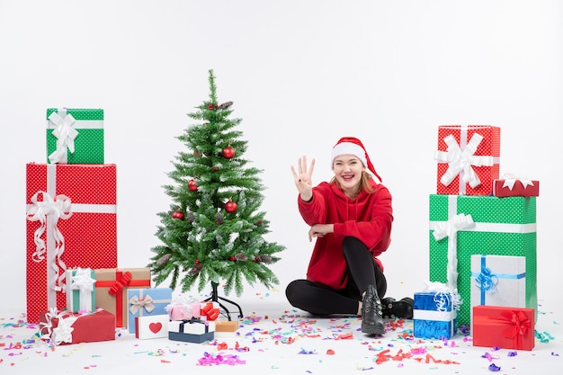 Вид спереди молодой женщины, сидящей вокруг праздничных подарков, считая на белой стене