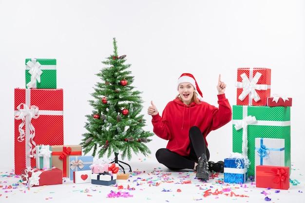 Вид спереди молодой женщины, сидящей вокруг праздничных подарков, возбужденных на белой стене