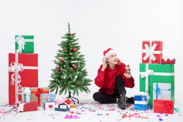 Вид спереди молодой женщины, сидящей вокруг праздничных подарков, что-то держит на белой стене