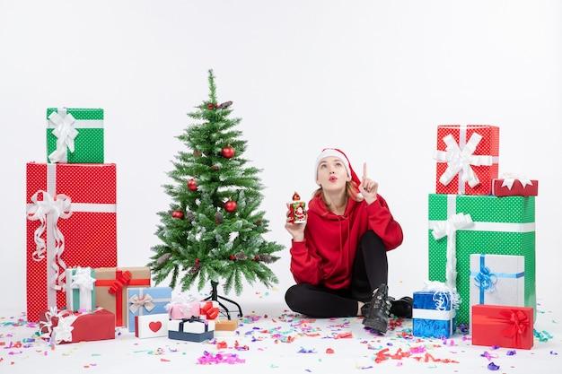 白い壁に何かを持って休日のプレゼントの周りに座っている若い女性の正面図