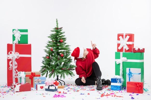 Вид спереди молодой женщины, сидящей вокруг праздничных подарков на белой стене