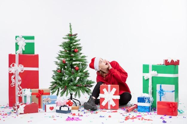휴일 주위에 앉아있는 젊은 여자의 전면보기 흰 벽에 선물