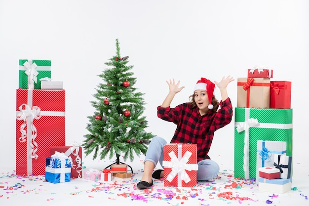 Вид спереди молодой женщины, сидящей вокруг подарков и маленькой праздничной елки на белой стене