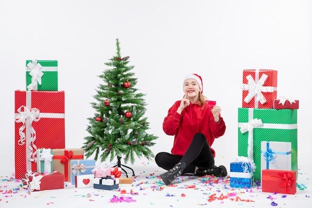흰 벽에 은행 카드를 들고 선물 주위에 앉아있는 젊은 여자의 전면보기