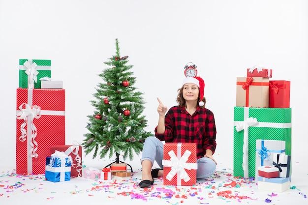 흰 벽에 그녀의 머리에 시계를 들고 선물 주위에 앉아 젊은 여자의 전면보기